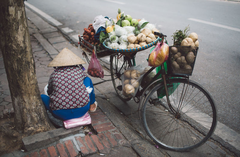 Rear view of person of selling fruits in basket on street