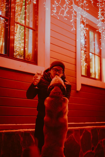 Man holding wineglass while standing by illuminated house with dog