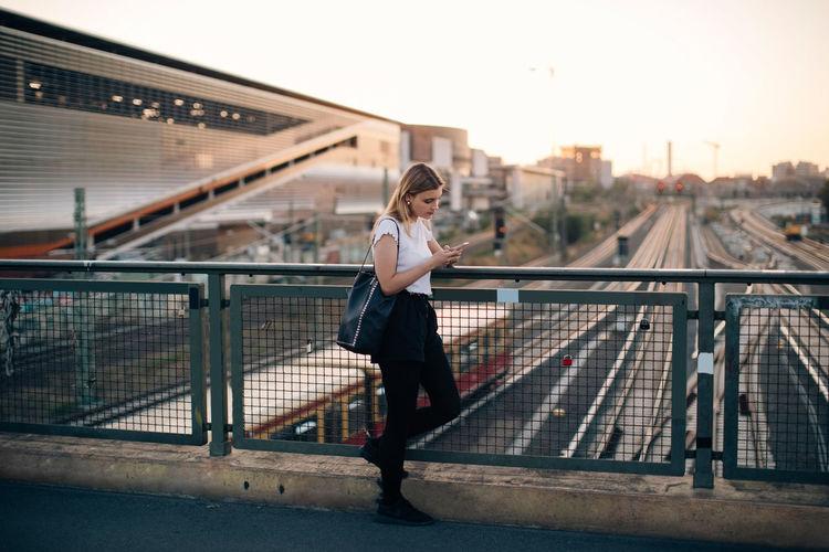 Full length of woman standing on footbridge in city