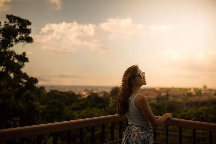 Woman standing by railing against sky during sunset