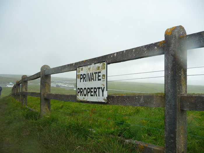Information sign on fence by sea against sky