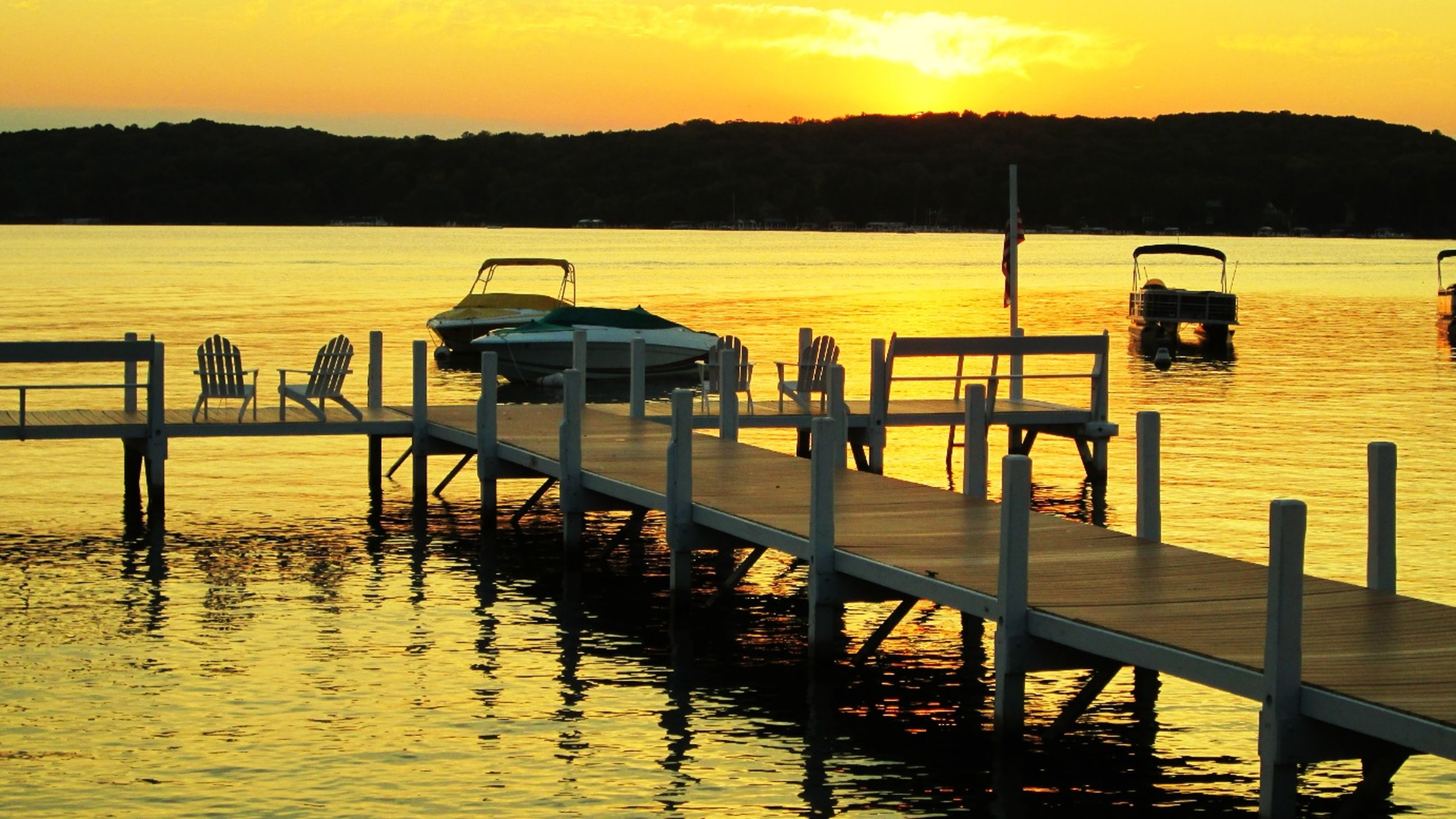 sunset, water, transportation, mode of transport, nautical vessel, tranquil scene, river, orange color, tranquility, scenics, waterfront, lake, sky, reflection, beauty in nature, boat, nature, pier, silhouette, yellow