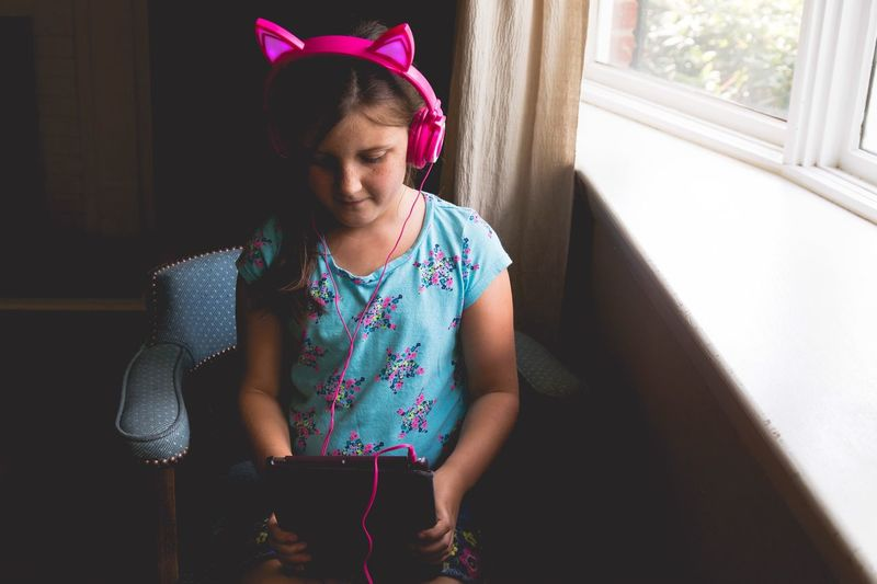 High Angle View Of Girl Using Digital Tablet While Listening To Pink Headphones At Home