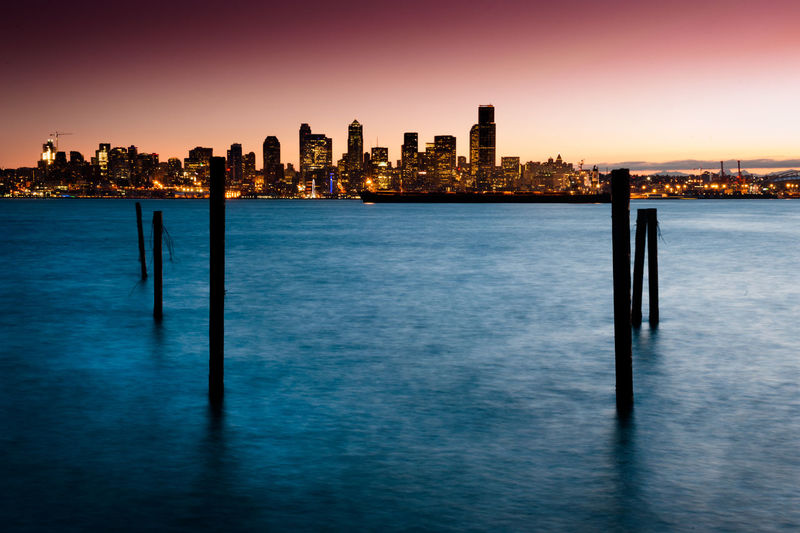 Silhouette Wooden Posts In Sea By Illuminated City Skyline Against Clear Sky During Sunset