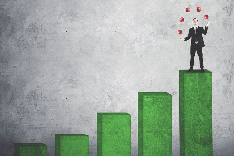 Businessman Juggling Balls On Green Graph Against Wall