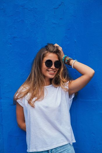 Portrait Of Smiling Young Woman In Sunglasses Standing Against Blue Wall