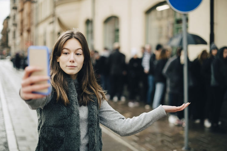 Portrait of woman holding smart phone while standing in city