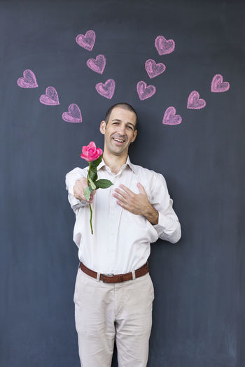 Single adult white man wearing a white shirt standing in front of a blackboard with painted hearts holding a rose. Concept of crazy love Love Romance Romantic Valentine Valentine's Day  Blackboard  Cheerful Flower Front View Happiness Heart Shape Holding Looking At Camera Love Love ♥ One Person Pink Color Portrait Rose - Flower Rose🌹 Smiling Standing Toothy Smile Valentine's Day - Holiday Valentines Day