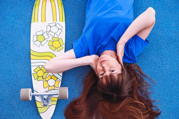 Portrait of young women with skateboard on blue background. woman wears blue t-shirt.