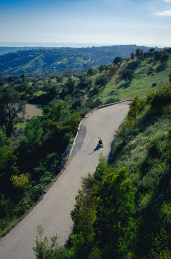 High Angle View Of Man Longboarding On Mountain Road