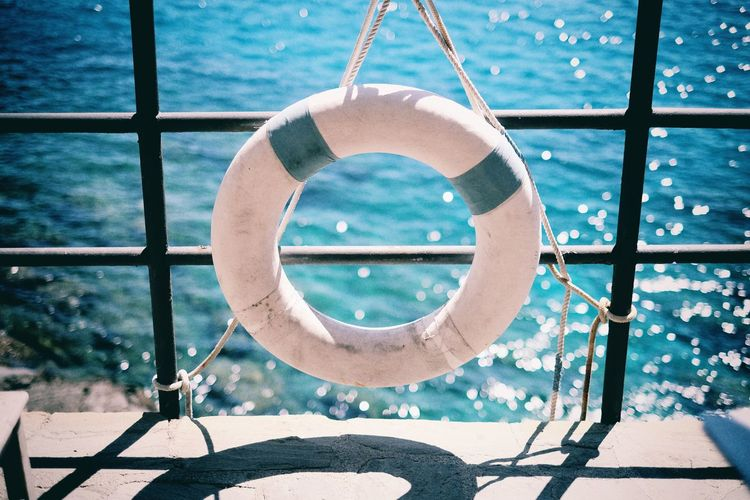 High Angle View Of White Inflatable Ring Hanging From Railing On Pier Against Sea
