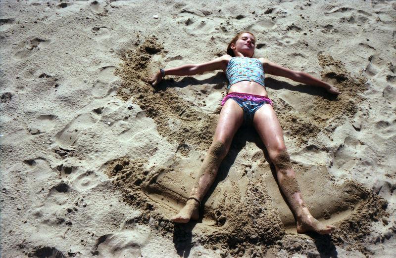 Girl lying on sand at beach