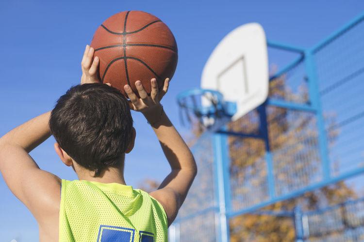 Low Angle View Of Boy Playing Basketball