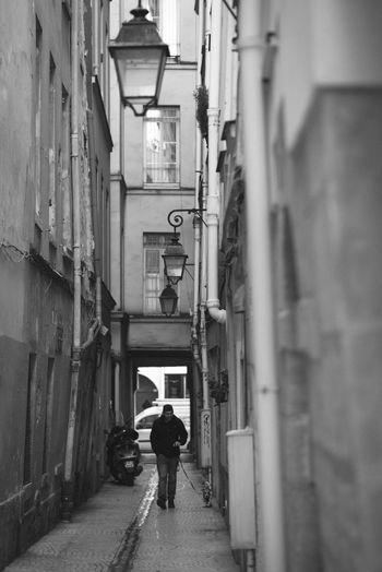 Man walking in alley amidst buildings
