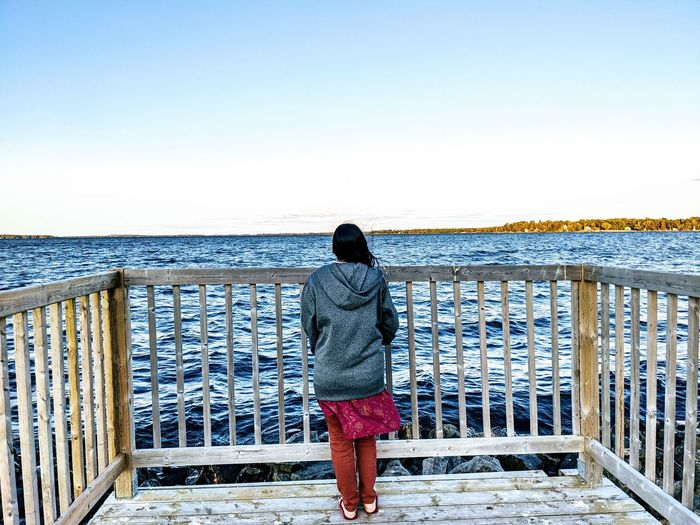 Rear view of woman standing by railing against sea