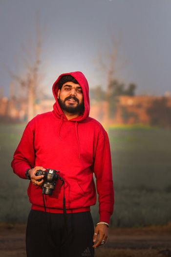 Portrait of young man holding camera while standing outdoors