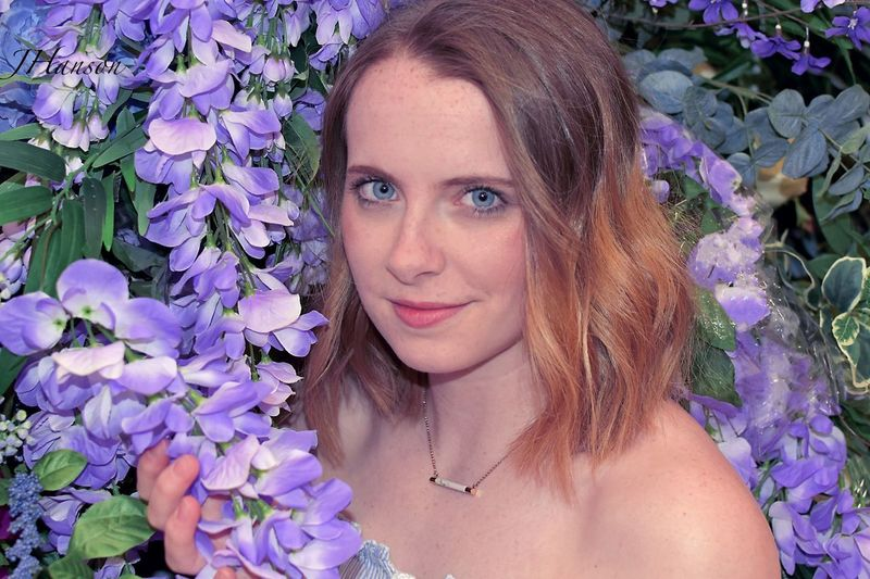Portrait of a smiling young woman with purple flower