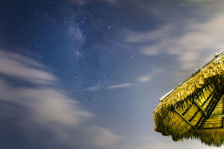 Low angle view of thatched roof against sky at night