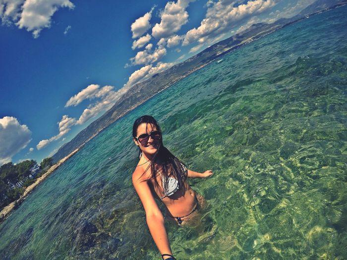 Portrait of young woman wearing bikini standing in sea