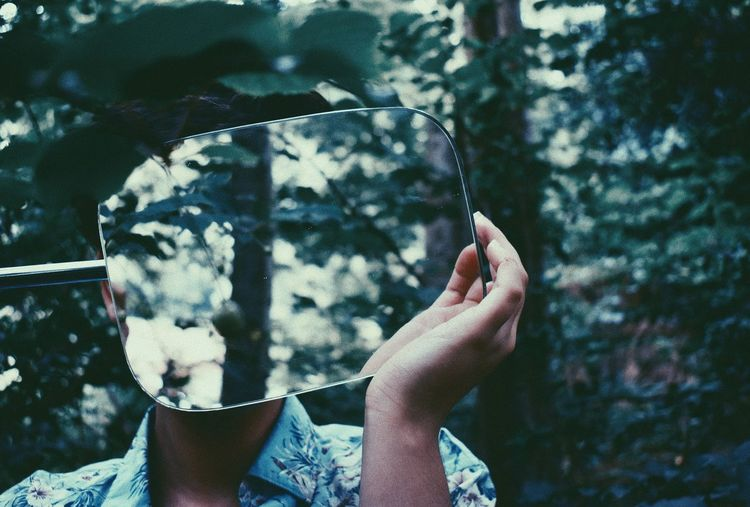 Woman holding mirror while standing in forest