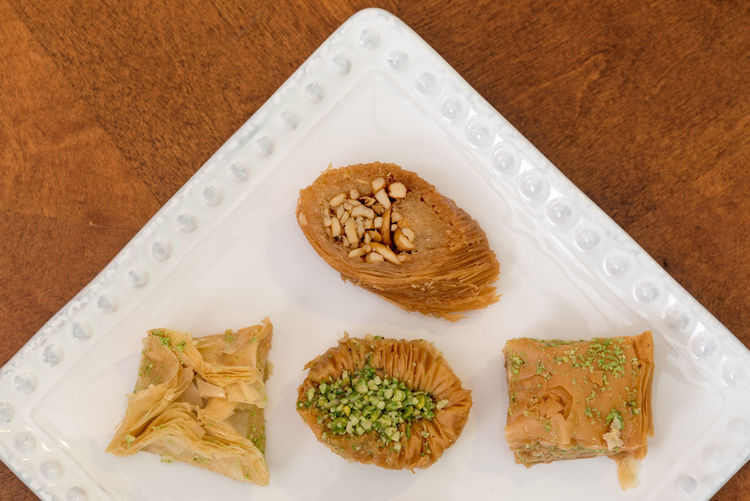 Delicious baklava covered with pistachio and almonds, displayed on a white plate, traditional Greek pastry, enjoyed best as dessert or after dinner. Almonds Baked Close-up Delicious Platter Diabetes Food Greek Sweets Indulgence No People Nuts Portion Ready-to-eat Serving Size Snack Sugar Sweets Unhealthy Eating
