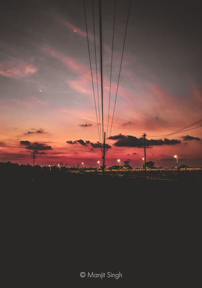 Silhouette electricity pylons on field against orange sky