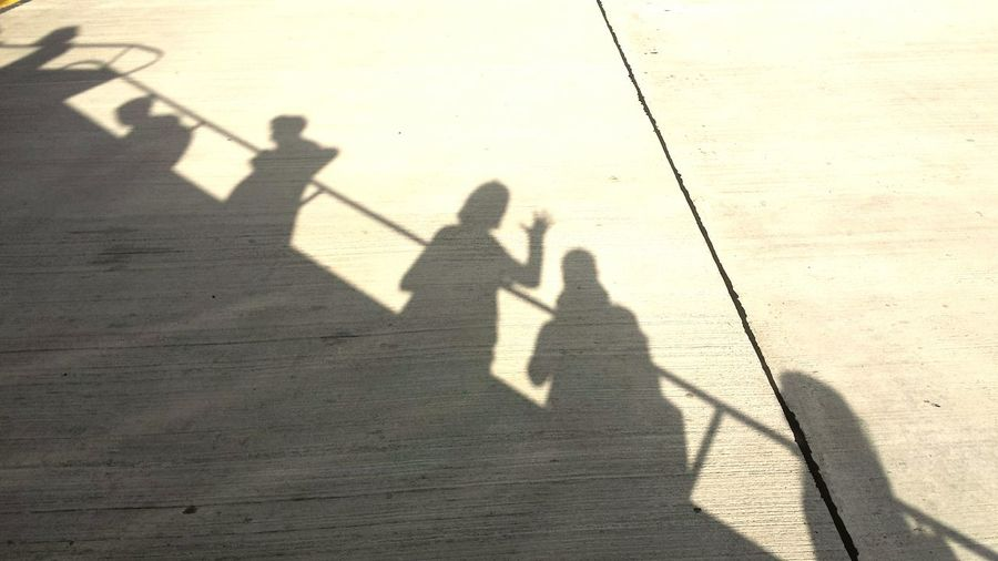 Low section of people standing by shadow