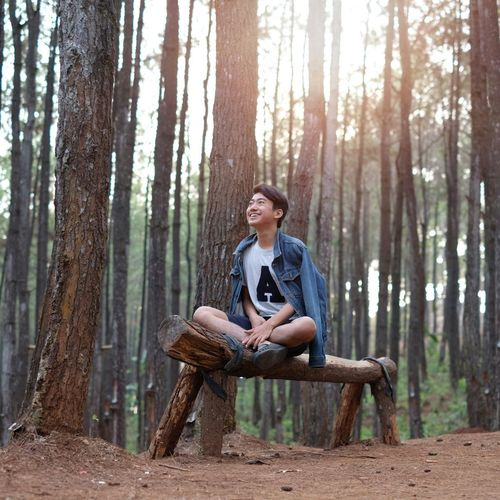 Happy teenage boy sitting on log in forest