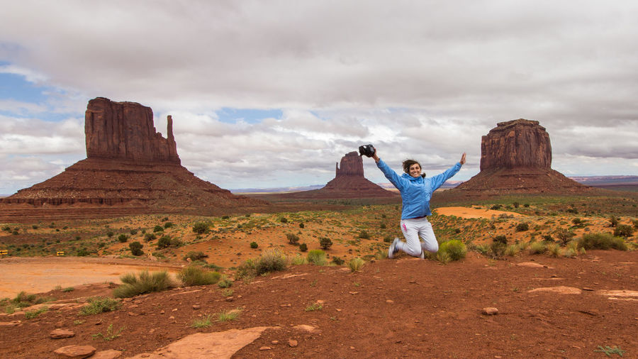 Portrait of cheerful woman with arms outstretched jumping on land against cloudy sky