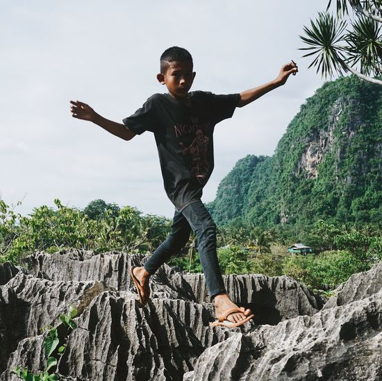 boy exploring the Rammang-Rammang carst site near Makassar, Sulawesi, Indonesia Adventure Arms Outstretched ASIA Beauty In Nature Boy Day Exploring Hidden Gems  Hidden Places INDONESIA Jumping Karst Formations Looking At Camera Makassar Mid-air One Person Outdoors Paradise Rammang Rammang Rock - Object Rock Formation Scenics Sulawesi Taman Batu Traveling The Portraitist - 2017 EyeEm Awards Connected By Travel An Eye For Travel