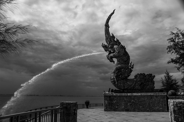 Low angle view of statue by sea against sky