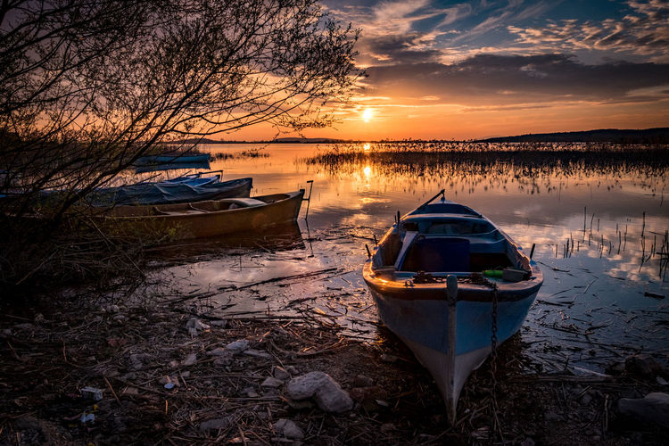 Boats on the lake under sunset. Water Nautical Vessel Sunset Moored Mode Of Transportation Transportation Sky Nature Beauty In Nature Reflection Beach Tranquility Cloud - Sky Scenics - Nature No People Lake Land Tranquil Scene Tree Outdoors Rowboat