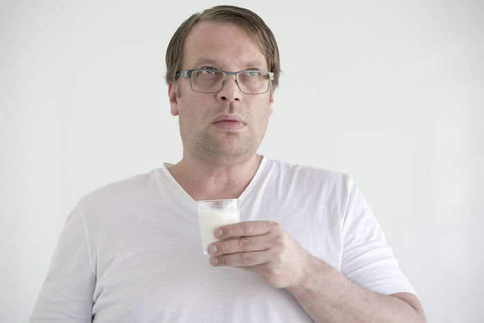 Man holding a glass of milk. Adult Casual Clothing Confusion Disbelief Emotional Stress Eyeglasses  Front View Glass Of Milk Healthy Food Holding Humor Lifestyles Looking Up Making A Face Man Milk One Man Only One Person Portrait Scientist Shock Studio Shot Surprise Terrified White Background