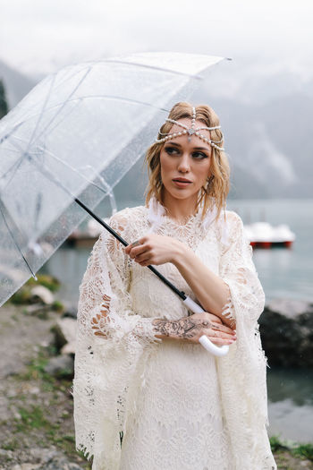 A tender sensual young woman bride in a fashionable wedding dress is standing in the rain in nature