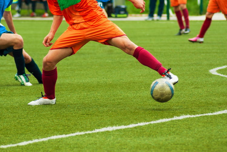 Low section of people playing soccer on field