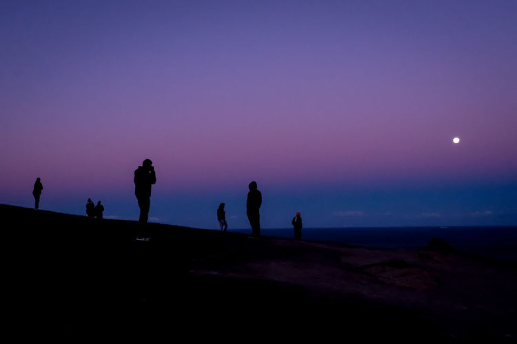 Silhouette people standing on shore against sky at sunset