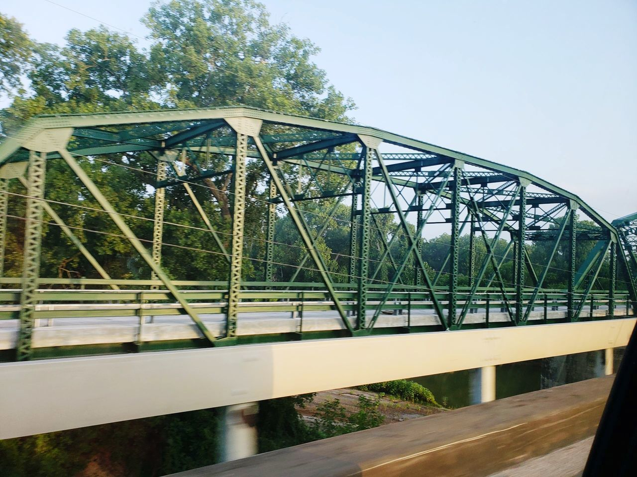 LOW ANGLE VIEW OF BRIDGE OVER RIVER AGAINST CLEAR SKY