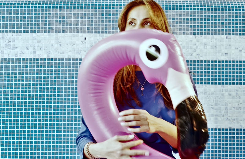 Woman looking away while holding inflatable raft
