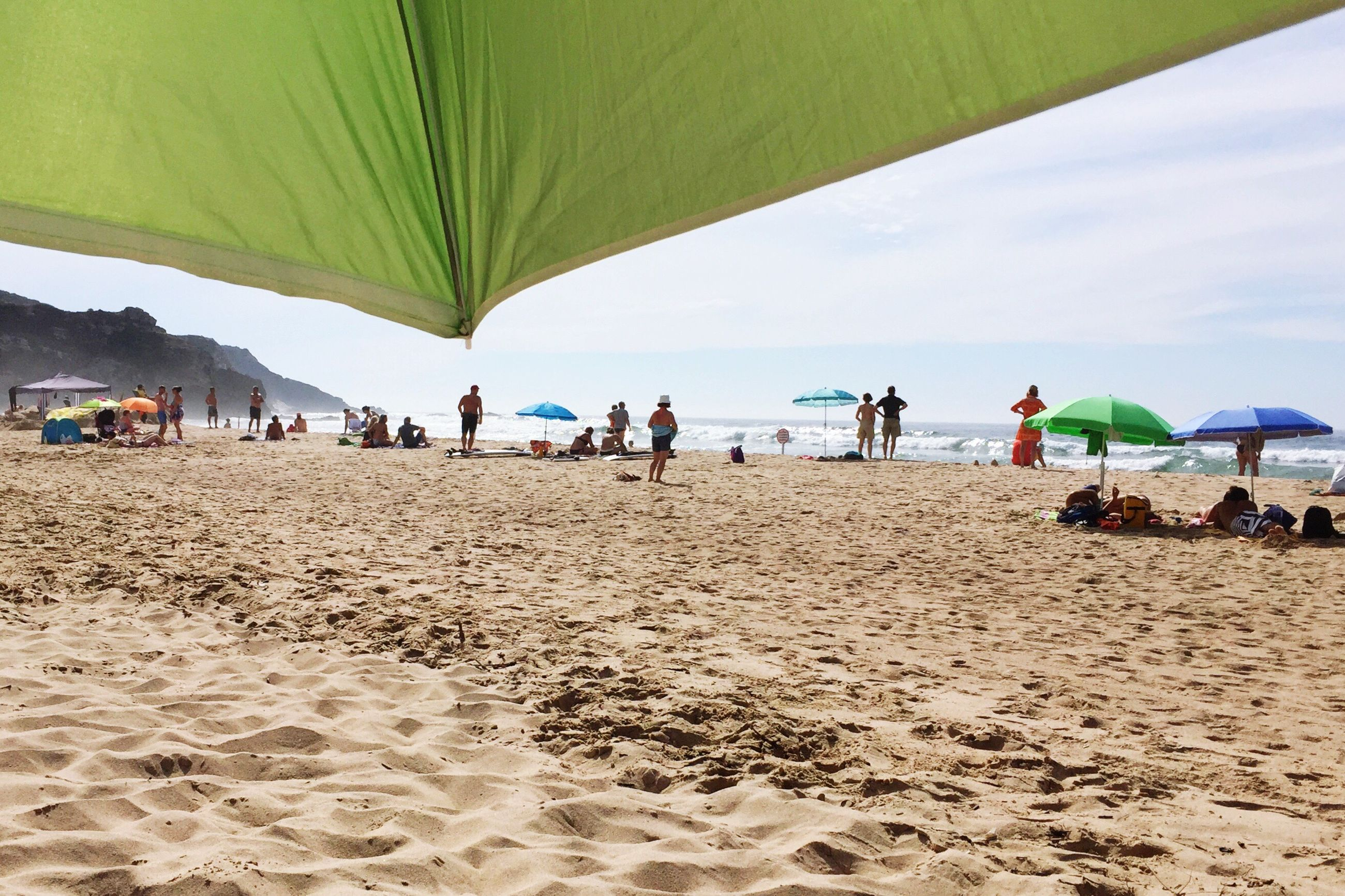beach, sand, parasol, travel, water, vacations, leisure activity, large group of people, lifestyles, sea, tourist, tourism, sunshade, enjoyment, beach holiday, cloud - sky, shore, day, sky, nature, weekend activities, tranquility, outdoors, green color, tranquil scene, enjoying