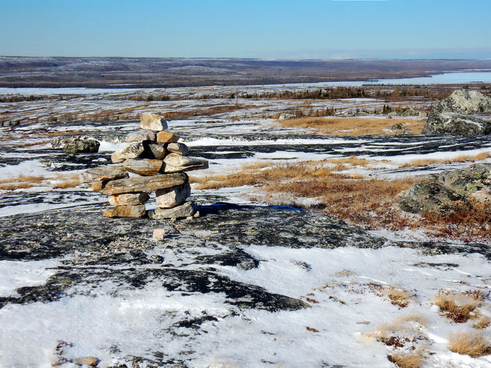 Inukshuk statue on the top of a mountain where the radar is in Kuujjuaq Inukshuk Inuksuk Kuujjuaq Sky Beauty In Nature Scenics - Nature Water Nature Day Solid No People Tranquil Scene Tranquility Rock Rock - Object Environment Non-urban Scene Landscape Stack Land Winter Outdoors Flowing Water Northern Quebec