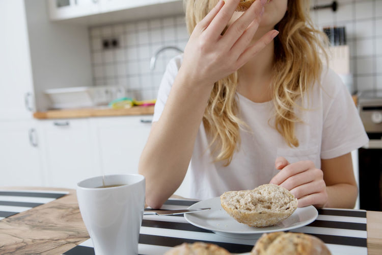 Midsection of woman having bread over dining table at home