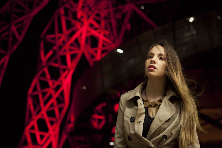 Low Angle View Of Beautiful Woman In Jacket Against Illuminated Metallic Structure