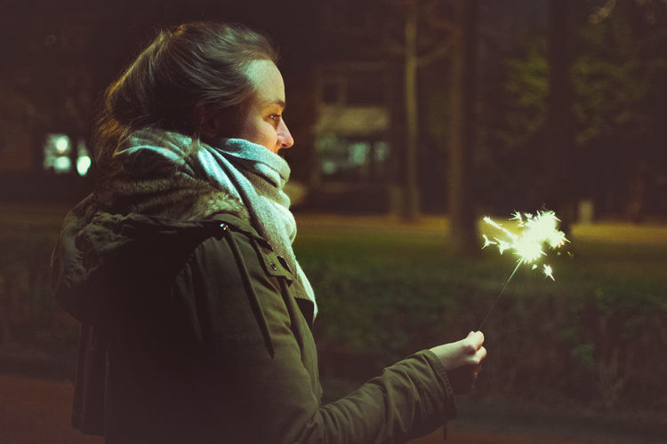 Side View Of Woman Looking At Sparkler At Night