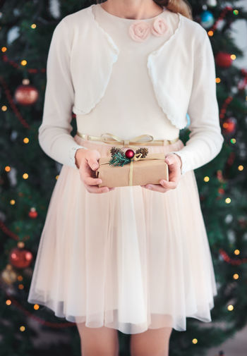 Midsection of a girl holding christmas present