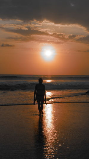 Silhouette woman walking at beach during sunset
