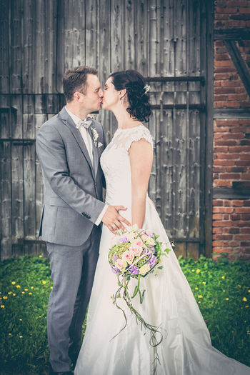 Bride And Groom Kissing While Standing On Grassy Field