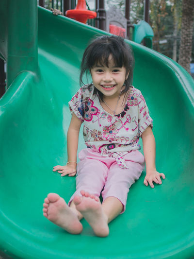 Cute little asian girl having fun on slide Childhood Child Girls One Person Front View Innocence Real People Females Women Smiling Leisure Activity Happiness Full Length Cute Looking At Camera Casual Clothing Portrait Emotion Lifestyles Outdoor Play Equipment Outdoors