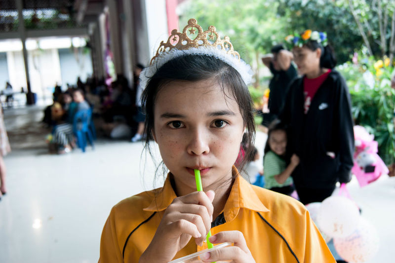 Portrait of girl wearing tiara drinking drink during party