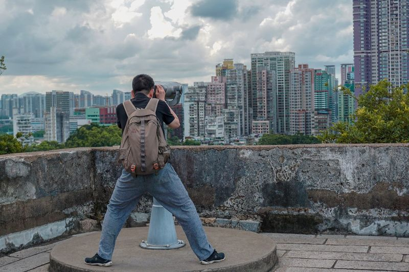Rear View Of Man Looking City Through Coin-Operated Binoculars