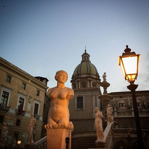 Low angle view of sculptures against palermo cathedral at dusk